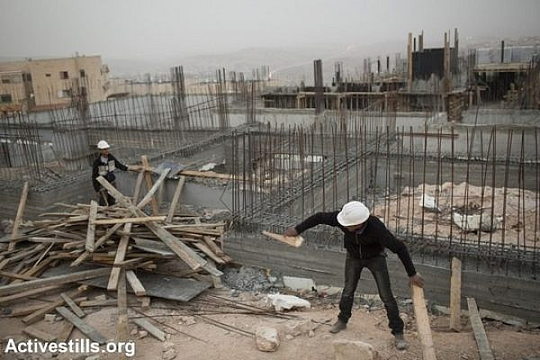 Palestinian construction workers work at a site in Jerusalem's Ramat Shlomo neighborhood. (Tali Mayer/Activestills.org)