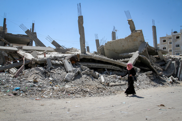 A Palestinian woman walks past the rubble of a home that was destroyed by Israel during the 2014 war, Rafah, Gaza Strip, July 30, 2015. (Abed Rahim Khatib / Flash 90)