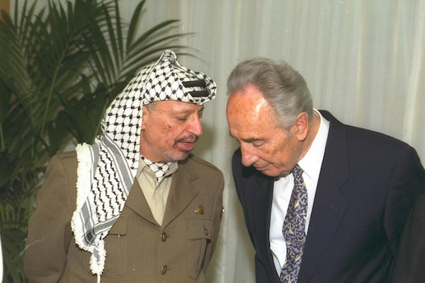 PLO Chairman Yasser Arafat speaks with then Foreign Minister Shimon Peres in Paris, July 6, 1994. (Sa'ar Yaacov/GPO)