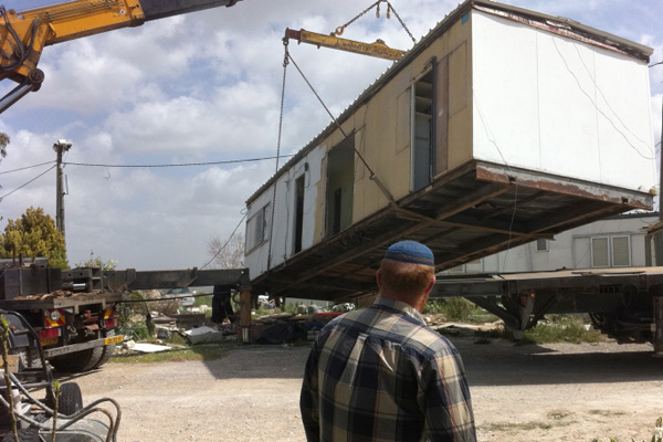A Jewish settler watches as a caravan home in the illegal outpost of Ramat Gilad is removed, after which it was relocated in a another West Bank settlement March 14, 2012. (Roy Sharon/Flash90)