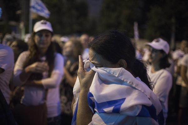 An Israeli woman breaks into tears as she covers herself in an Israeli flag during a rally marking two years since Israeli soldier Oron Shaul was taken captive by Hamas, at the protest tent outside the Prime Minister Benjamin Netanyahu's residence, Jerusalem, July 20, 2016. (Hadas Parush/Flash90)