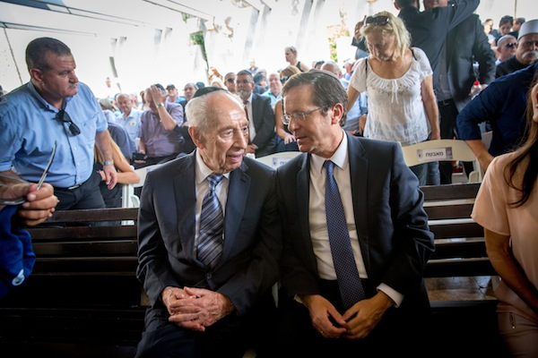 Former Israeli President Shimon Peres is seen with opposition leader Isaac Herzog at the funeral of former Knesset member Binyamin Fuad Ben-Eliezer at the Holon cemetery, August 30, 2016. (Miriam Alster/Flash90)