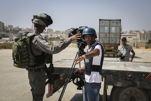 An Israeli Border Police officer harasses a Palestinians journalist covering clashes between Palestinian protesters and Israeli security forces outside Ofer Military Prison, near Betunia, West Bank, August 3, 2016. (Flash90)