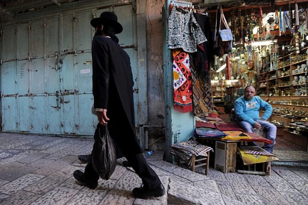 Illustrative photo of an ultra-Orthodox Jewish man walking past an Arab shopkeeper in the Old City of Jerusalem. (Gil Yaari/Flash90)