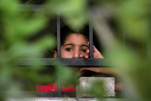 A young Palestinian boy looks through a window at a funeral for family members who were killed by an Israeli air strike in Gaza, August 27, 2014. (Abed Rahim Khatib/Flash90)