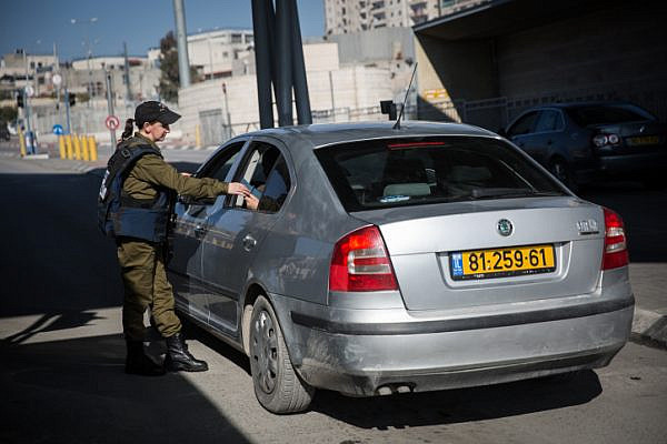 An Israeli soldier at a checkpoint examines the ID cards of '48 Palestinians traveling in a car with yellow, Israeli license plates. (Illustrative photo by Hadas Parush/Flash90)