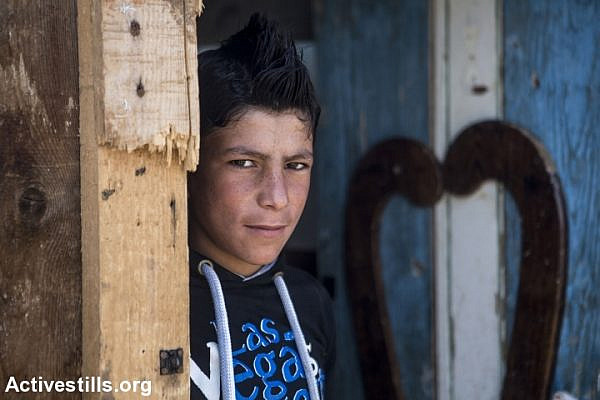 A Syrian teenager in front of his shelter in one informal camp for Syrian refugees in the Bekaa Valley, near the village of Jib Janin, eastern Lebanon, April 14, 2016. (Anne Paq/Activestills.org)