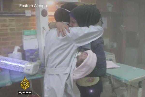 Nurses console each other as they evacuate babies during a regime attack on a children's hospital in Aleppo. (Al Jazeera screenshot)