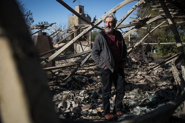 Israeli artist Yoram Ra'anan stands in what remains of his studio, which burned down completely in an overnight fire in Beit Meir, outside of Jerusalem, November 25, 2016. (Hadas Parush/Flash90)