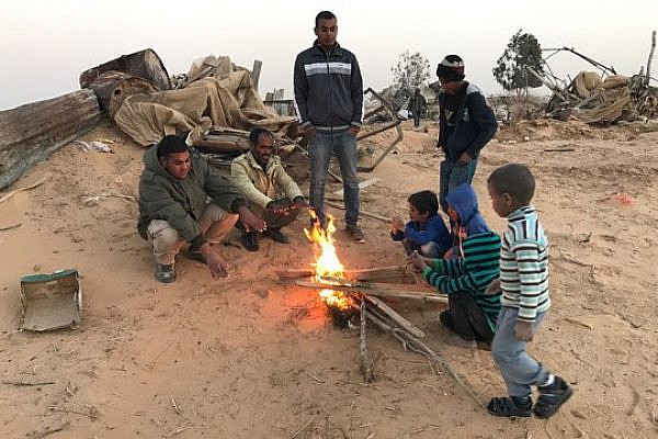 Residents of Bir Hadaj warm themselves around a fire after homes in the village were demolished. (Rami Younis)