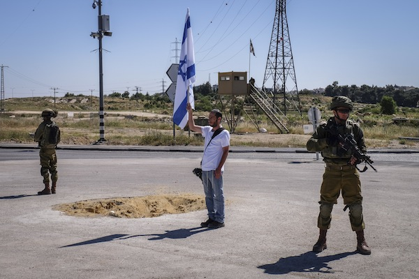 Israeli soldiers and pedestrians stand still at the Gush Etzion Junction, West Bank, as a two-minute siren is sounded across Israel to mark Holocaust Remembrance Day, May 5, 2016. (Gershon Elinson/Flash90)