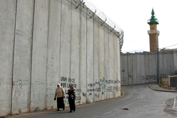 Two Palestinian women walk along Israel's separation wall in the West Bank village of Abu Dis. (Anna Kaplan/Flash90)