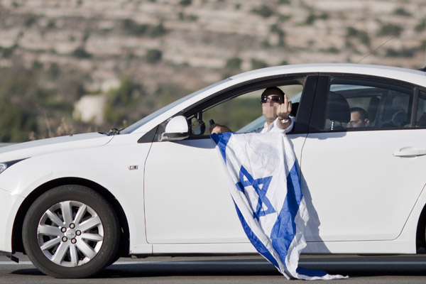 An Israeli man makes a lewd gesture toward a joint Israeli-Palestinian peace march in the West Bank, November 27, 2015. (Mustafa Bader/Activestills.org)