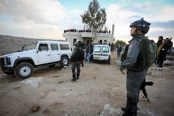 Members of Israeli security forces takes position during clashes with Palestinian protesters after attempting to demolish a house which Israeli authorities said was built without permission. Dozens of women can be seen lining the house in the background, Budrus, West Bank, January 4, 2017. (Flash90)