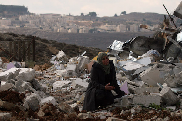 A Palestinian woman sits on rubble of a structure after it was razed by the Israeli army and Civil Administration in the East Jerusalem neighborhood of Beit Hanina, on the outskirts of the West Bank, November 24, 2011. (Issam Rimawi/FLASH90)