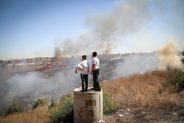 Ultra-Orthodox children look on as fire fighters try to extinguish a fire tha broke out near Ramat Beit Shemesh, outside of Jerusalem, September 20, 2016. (Yaakov Lederman/Flash90)
