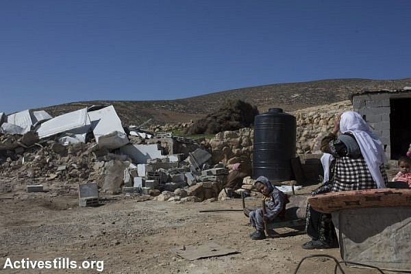 Palestinians sit next to their demolished home after it was torn down by Israeli bulldozers in the village of Khirbet al-Halawah, 'Firing Zone 918,' south Hebron Hills, West Bank, February 3, 2016. (Oren Ziv/Activestills.org)