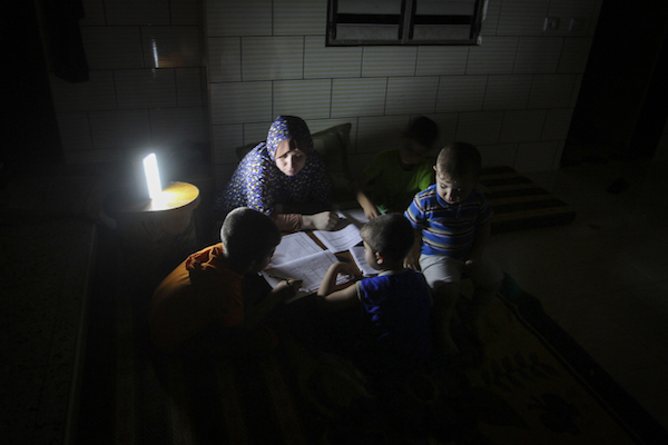 Palestinian students study next to a lantern during a power outage in Rafah, Gaza Strip, May 18, 2016. (Abed Rahim Khatib/Flash90)