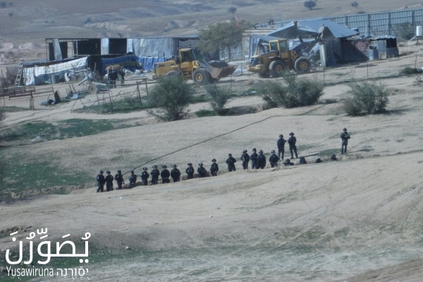Israeli police officers stand guard as bulldozers demolish homes in Umm el-Hiran, January 18, 2017. (Yuṣawiruna Project, Negev Coexistence Forum)