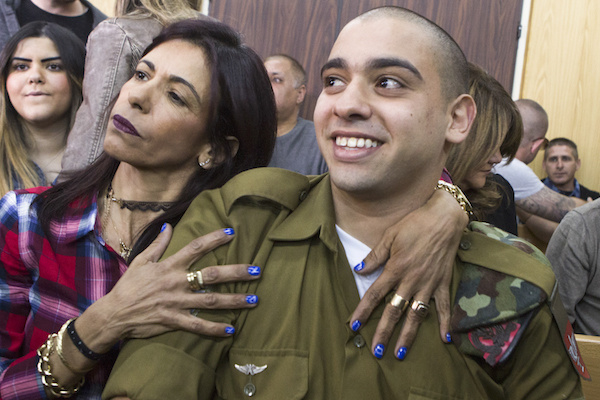 Elor Azaria, the Israeli soldier who shot dead a disarmed and injured Palestinian attacker in the West Bank city of Hebron on March 24, 2016, is surrounded by family and friends as he awaits to hear his sentence in a courtroom at the Kirya military base in Tel Aviv, on February 21, 2017. (Jim Hollander/POOL)