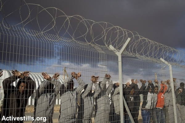 African asylum seekers jailed in the Holot detention center protest behind the prison's fence, February 17, 2014. (Photo by Activestills.org)