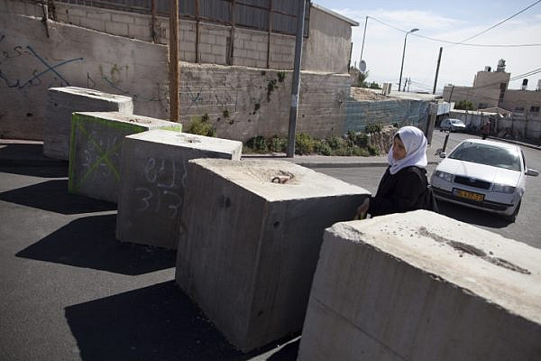 A Palestinian woman passes through concrete blocks that were installed by Israeli police in the East Jerusalem neighborhood of Jabal Mukaber, October 21, 2015. (Lior Mizrahi/Flash90)