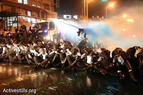 Police spray ultra-Orthodox demonstrators with blue liquid during a protest against the arrest of a Haredi IDF deserter, Jerusalem, March 23, 2017. (Oren Ziv/Activestills.org)