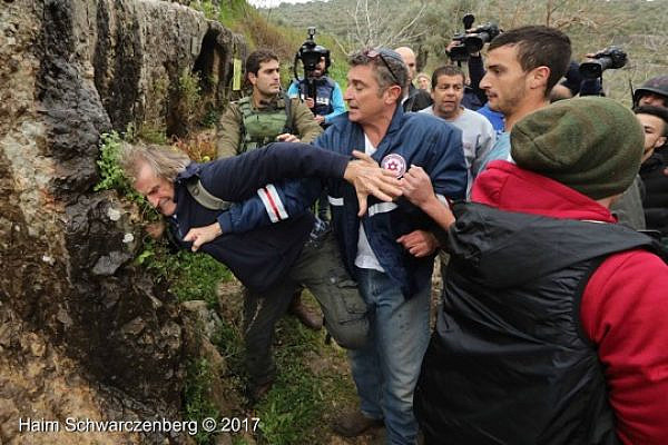 An Israeli settler in a Magen David Adom uniform attacks a left-wing demonstrator during a protest in Nabi Saleh, March 3, 2017. (Haim Schwarczenberg)