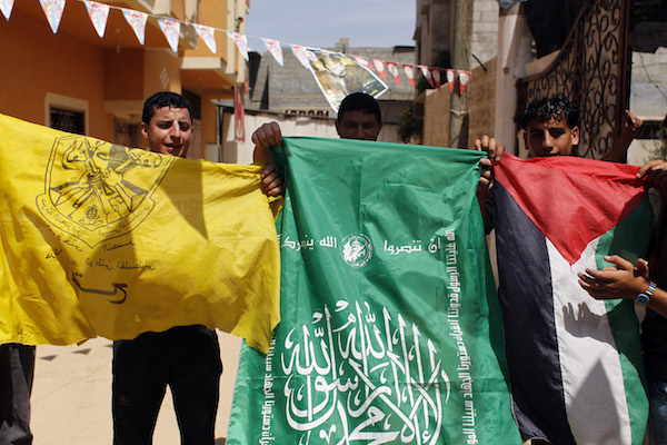 Palestinian protesters wave the flags of Palestinian political movements, Fatah (yellow) and Hamas (green) as they chant slogans in support of the national reconciliation and the announcement of the formation of a national unity government between the two factions, in Khan Yunis, in the southern Gaza Strip, on May 29, 2014. (Abed Rahim Khatib/Flash90)