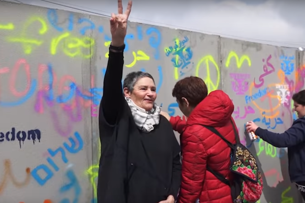 Robi Damelin, from the Bereaved Families Forum, is seen pictured in front of a model separation wall during an International Women's Day action in the West Bank city of Beit Jala.