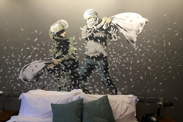 Banksy artwork showing an Israeli soldier and a Palestinian having a pillow fight, The Walled Off Hotel, Bethlehem, March 3, 2017. (Haggai Matar)