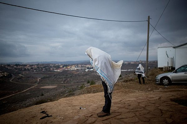 Jewish men pray early in the morning on the hill overlooking Ofra in the Jewish settlement of Amona, West Bank, December 18, 2016. (Miriam Alster/Flash90)