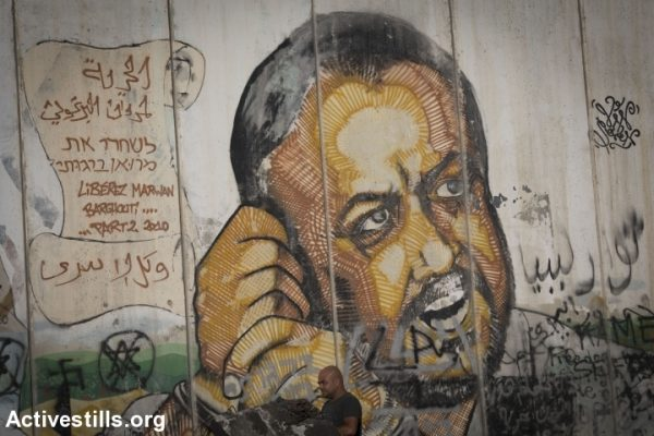 A mural of Marwan Barghouti on the separation wall at Qalandiya checkpoint, West Bank, June 10, 2016. (Oren Ziv/Activestills.org)