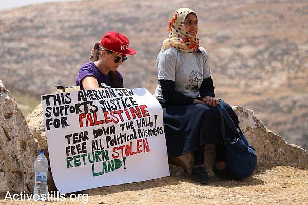 A diaspora Jewish activist sits beside a Palestinian woman at the Sumud Freedom Camp, Sarura, West Bank, May 19, 2017.