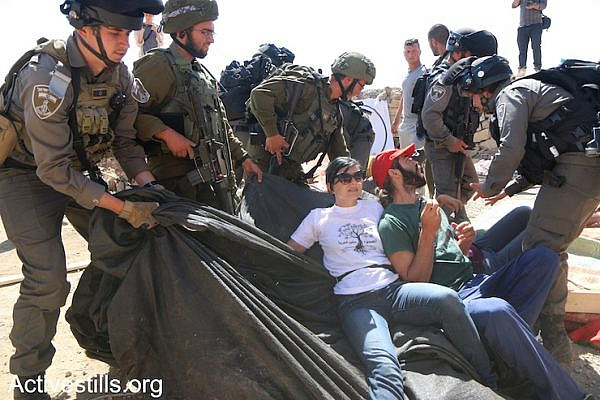 Palestinians, Israelis, and diaspora Jewish activists confront the Israeli army during a raid on Sumud Freedom Camp, Sarura, West Bank, May 25, 2017. (Ahmad al-Bazz/Activestills.org)