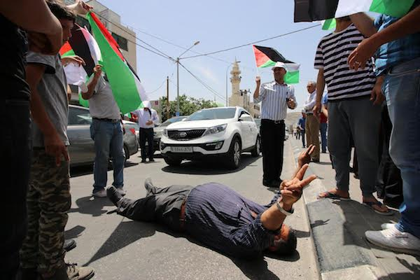 A Palestinian demonstrator gestures while lying on the ground during a protest in solidarity with hunger striking Palestinian prisoners, near Huwwara, West Bank, May 18, 2017. (Ahmad al-Bazz/Activestills.org)