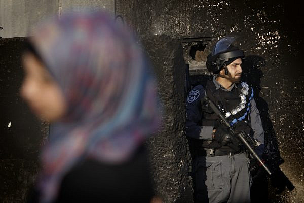 An Israeli soldier stands guard at the Qalandia checkpoint on the outskirts of the West Bank city of Ramallah as Palestinian muslim worshippers wait to cross the checkpoint to head to Al-Aqsa compound in Jerusalem's Old City to attend the first Friday prayers of Ramadan. July 4, 2014. (Miriam Alster/ Flash90)