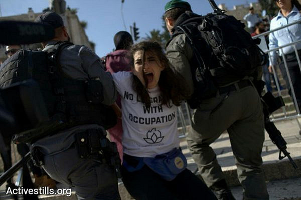 An activist with IfNotNow is carried away by Israeli police during a Jerusalem Day protest, Jerusalem, May 24, 2017. (JC/Activestills.org)