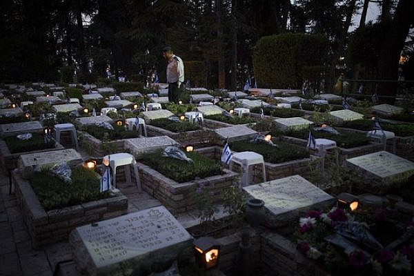 An Israeli soldier walks near graves of fallen soldiers in Mount Herzl Military Cemetery in Jerusalem, on April 30, 2017. (Yonatan Sindel/Flash90)