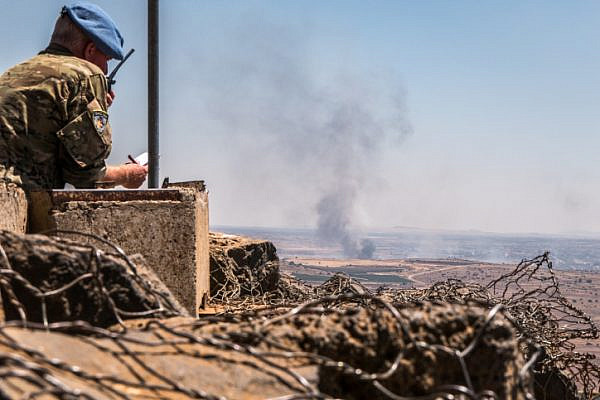 A UN observer looks at a lookout point as smoke rising at a Syrian village near the Israeli-Syrian border in the Golan Heights during fights between the rebels and the Syrian army, June 25, 2017. (Basel Awidat/Flash90)