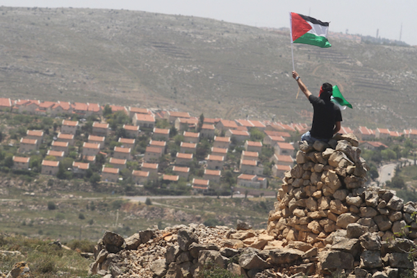 A Palestinian demonstrator from the West Bank village of Deir Jarir, northeast of Ramallah, waves a Palestinian flag as he sits on a pile of rocks during clashes with Israeli soldiers following a march against construction on Palestinian land by members of the Jewish settlement of Ofra on April 26, 2013. (Issam Rimawi/FLASH90)