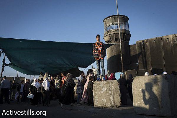Palestinian women and children, along with men over the age of 40, walk through Qalandiya checkpoint toward Jerusalem on the first Friday of Ramadan, June 2, 2017. (Oren Ziv/Activestills.org)