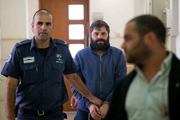 Prison guards escort Yosef Haim Ben-David, the third defendant in the murder of Muhammed Abu Khdeir, arrives to the Disctrict Court in Jerusalem, on April 5, 2016. Abu Khdeir, 16, a Palestinian teenager was abducted and killed in Jerusalem more then a year ago. His murder sparked violent protests in Arab areas of Jerusalem and northern Israel. (Yonatan Sindel/Flash90)