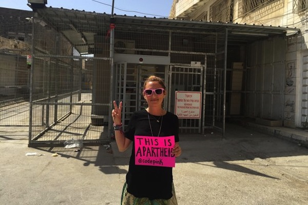 Jewish American activist Ariel Gold stands in front of an Israeli checkpoint in Hebron.
