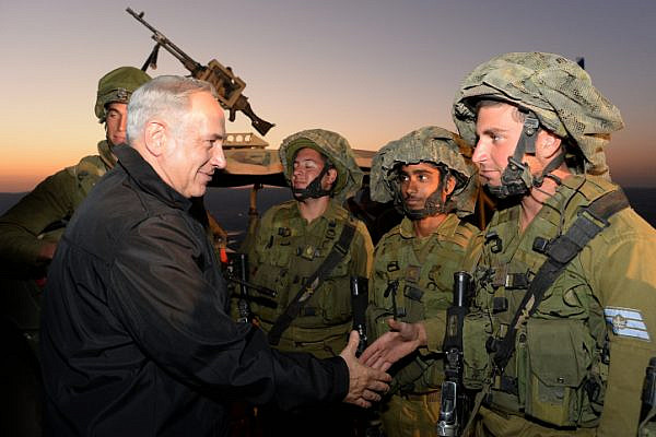 Prime Minister Benjamin Netanyahu seen with Israeli soldiers of the IDF Armored Corps during an army exercise in the Golan Heights, northern israel on October 15, 2013. (Kobi Gideon/GPO)