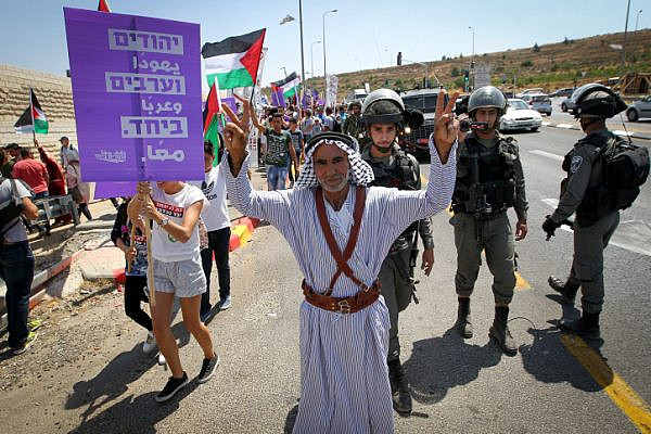 Palestinian and Israeli activists take part a protest against occupation, Route 60, between Jerusalem and the West Bank city of Bethlehem, July 7, 2017. (Wisam Hashlamoun/Flash90)