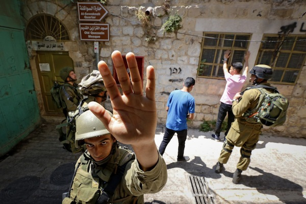 An Israeli soldier attempts to block the view of a photographer as Israeli soldiers search Palestinian men in the West Bank city of Hebron, June 22, 2017. (Wisam Hashlamoun/Flash90)