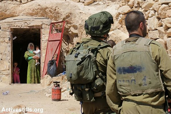 Israeli soldiers stand in front a cave in Sarura, where a Palestinian family lives, during the second military raid on Sumud Freedom Camp, May 25, 2017. (Ahmad al-Bazz/Activestills.org)