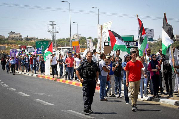 Hundreds of Palestinian and Israeli activists march in an anti-occupation, pro-peace rally on Road 60, the West Bank's main north-south highway, July 7, 2017. (Wisam Hashlamoun/Flash90)