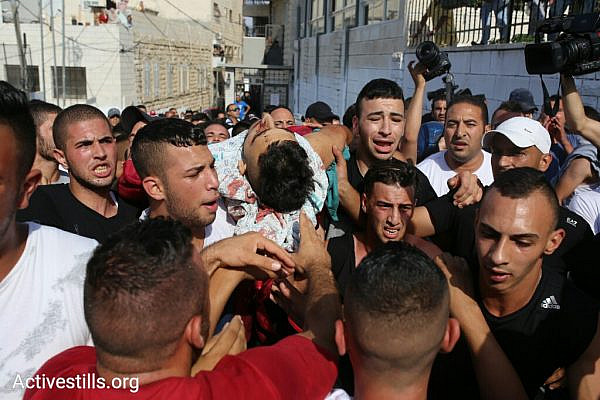 Palestinians in A-Tur, East Jerusalem retrieve the body of a slain Palestinian demonstrator from Makassed Hospital for burial, after he was shot and killed by Israeli forces during a demonstration against the Israeli closure of the Al-Aqsa compound, July 21, 2017. (Oren Ziv/Activestills.org)